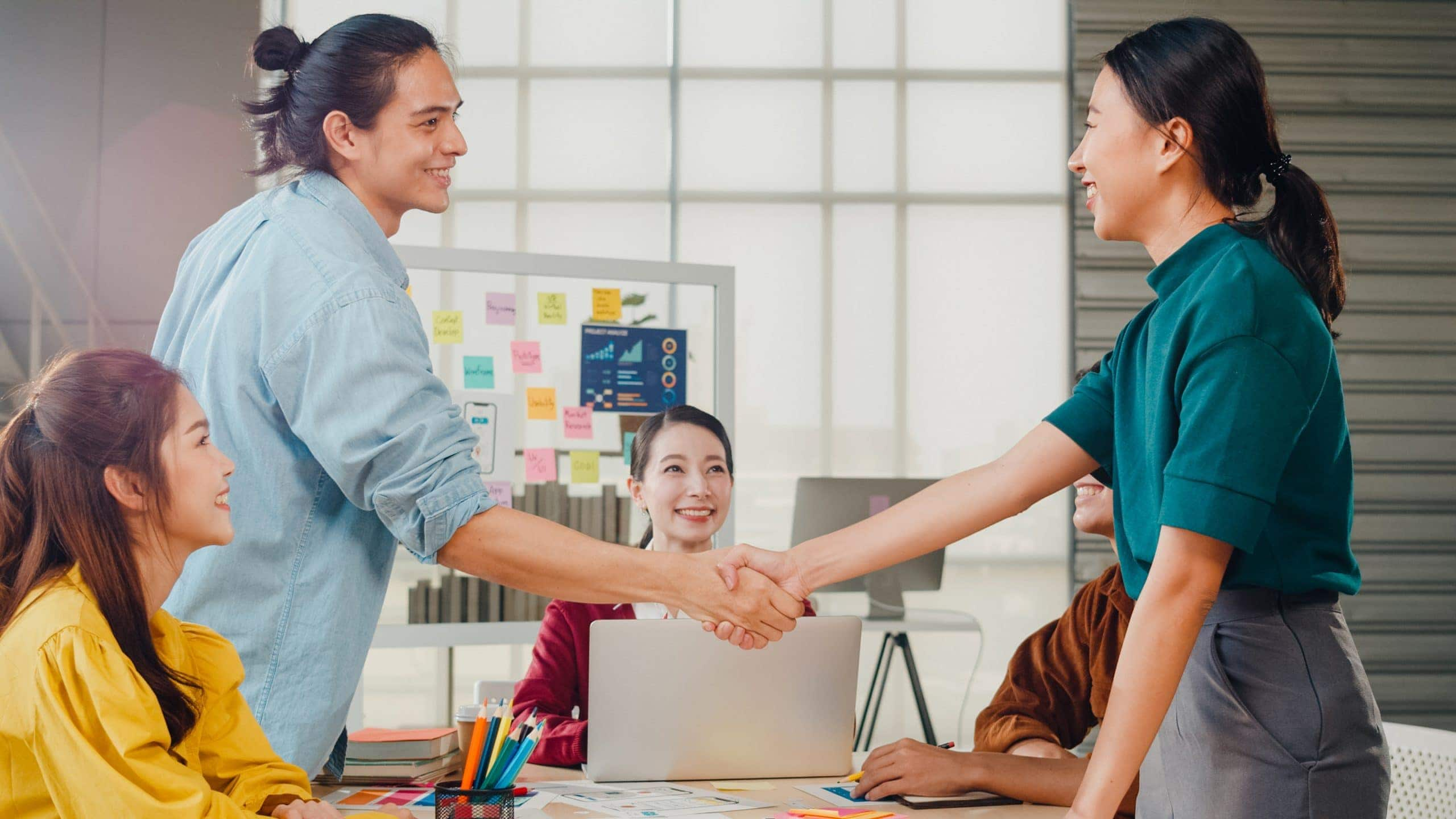 multiracial group young creative people smart casual wear discussing business shaking hands together smiling while standing modern office partner cooperation coworker teamwork concept scaled